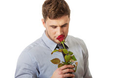 Handsome man holding red rose. Young handsome man holding red rose Stock Photo