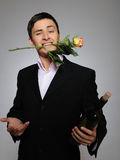 Handsome man holding rose flower and vine bottle Stock Images
