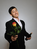 Handsome man holding rose flower and vine bottle Stock Photos