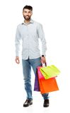 Handsome man holding shopping bags on white background Royalty Free Stock Images