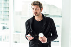 Handsome man holding smartphone and disposable cup Stock Photography