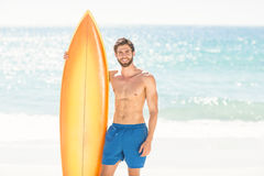 Handsome man holding surfboard Stock Photos