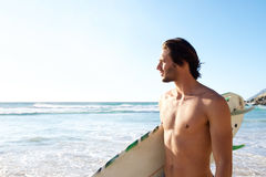 Handsome man holding surfboard at beach Stock Photo