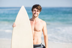 Handsome man holding surfboard on the beach Royalty Free Stock Images