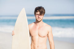 Handsome man holding surfboard on the beach. On a sunny day Stock Photos
