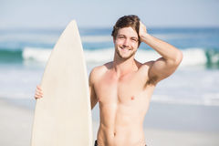 Handsome man holding surfboard on the beach Royalty Free Stock Image