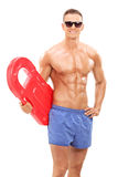 Handsome man holding a swimming float. Vertical shot of a handsome man holding a swimming float isolated on white background royalty free stock photo