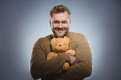 Handsome man is holding a teddy bear and smiling on gray background Stock Images
