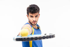 Handsome man holding tennis racket with ball Stock Photos