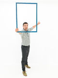 Handsome man holding a wooden frame Royalty Free Stock Images