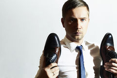 Handsome man holds shoes.Businessman in tie Stock Photo