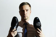 Handsome man holds shoes.Businessman in tie Royalty Free Stock Image