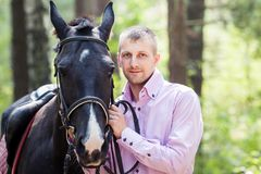 Handsome man and horse. Handsome man in pink shirt hold black horse in green forest Stock Photo