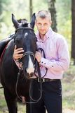 Handsome man and horse Stock Images