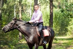 Handsome man on horse. Handsome man in pink shirt ride on the black horse in green forest Royalty Free Stock Photo