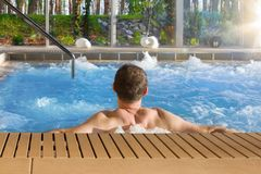 Handsome man in hot tub spa in luxurious hotel with big glass wi. Ndows with nature view royalty free stock images