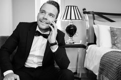 Man wearing tuxedo in hotel room talking on mobile phone, cellphone royalty free stock photo