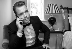 Serious Man wearing tuxedo in hotel room talking on mobile phone, cellphone Stock Photography
