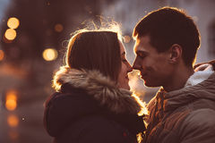 Handsome man hugging his girlfriend on bench in autumn park at night Royalty Free Stock Photo