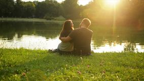 Handsome Man is Hugging His Girlfriend Sitting near the Lake in the City Park During Beautiful Sunset. Back View of stock video