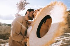 Handsome man hugging and kissing girlfriend. With straw hat and bouquet on sunny day with backlit royalty free stock photo