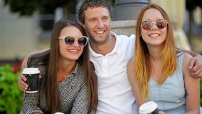 Handsome man is hugging two pretty girls in fashionable sunglasses. Three smiling friends posing looking at the camera stock footage