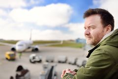 Middle age dude looking at aircraft in International airport. Handsome man in International airport. Male passenger at gate while waiting for his flight. Middle Royalty Free Stock Photos