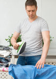 Handsome man ironing clothes. Stock Photography