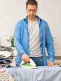 Handsome man ironing clothes. Stock Photos