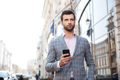 Handsome man in a jacket walking and holding mobile phone Stock Image
