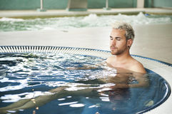 Handsome man in jacuzzi Stock Image