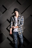 Handsome man in jeans, hat and shirt on grey background Royalty Free Stock Photos