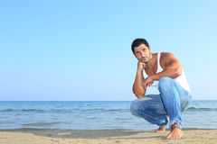 Handsome man in jeans by the sea Stock Photography