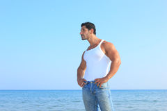 Handsome man in jeans by the sea Royalty Free Stock Image