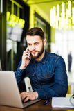 Handsome man in jeans shirt sitting in cafe holding a mobile phone , laptop, headphones and notebook with pan on wooden table. Royalty Free Stock Photography