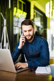 Handsome man in jeans shirt sitting in cafe holding a mobile phone , laptop, headphones and notebook with pan on wooden table. Stock Photo