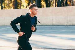 Handsome man jogging alone training for marathon Stock Images