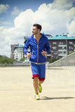 Handsome man jogging outdoors Stock Image