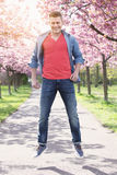 Handsome man jumping outdoors next to cherry blossom Stock Image