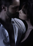 Handsome man kissing a beautiful woman Stock Images