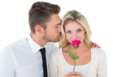 Handsome man kissing girlfriend on cheek holding a rose Royalty Free Stock Image
