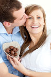 Handsome man kissing girlfriend holding chocolate. Handsome man kissing his girlfriend holding chocolate sitting against a white background Royalty Free Stock Photos