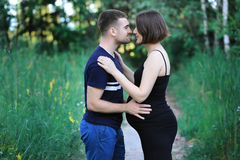 Handsome man is kissing his beautiful pregnant wife. Royalty Free Stock Photo