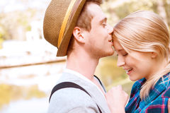 Handsome man kissing his girlfriend on forehead Stock Photos
