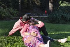 Handsome man kissing his pregnant wife in the park stock photo