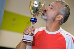 Handsome man kissing trophy. Handsome man kissing a trophy Royalty Free Stock Image