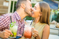 Handsome man kissing young happy woman at fashion cocktail bar. Handsome men kissing young women at fashion cocktail bar - Happy couple of lovers at beginning of Stock Image