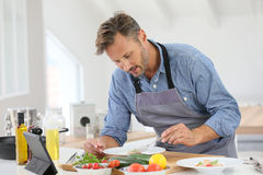 Handsome man in the kitchen cooking Royalty Free Stock Images