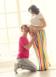 Handsome man kneeling and listening to the belly of pregnant wif Royalty Free Stock Photos