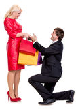 Handsome man on knees presenting woman gifts Stock Photos